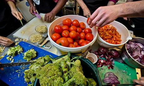 mesa com legumes a ser preparados por várias mãos